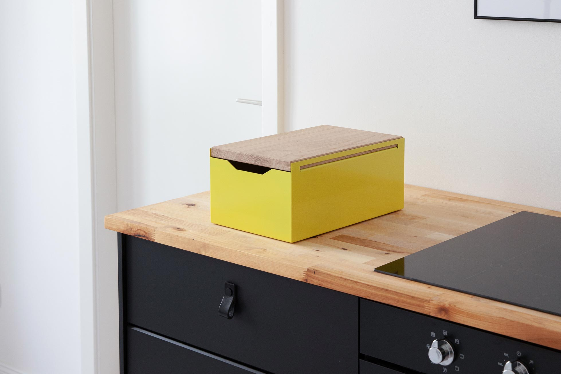 The Bread Box / Yellow shown here on a wooden countertop of a black kitchenette - Fantastic Frank Furnished Apartment.