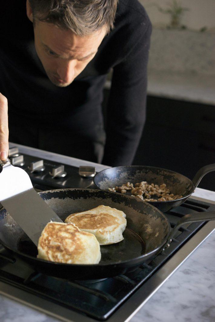 Sven Hausherr schwenkt den flaumigen Ricotta-Pfannkuchen, während er Walnüsse röstet.